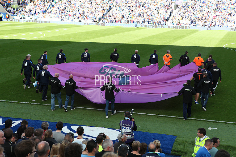 A giant goalkeepers shirt with the name Grimstone is carried onto the pitch before as part of the tribute to Matt Grimstone and Jacob Schilt who were killed in the Shoreham air disaster before the Sky Bet Championship match between Brighton and Hove Albion and Hull City at the American Express Community Stadium, Brighton and Hove, England on 12 September 2015. Photo by Bennett Dean.