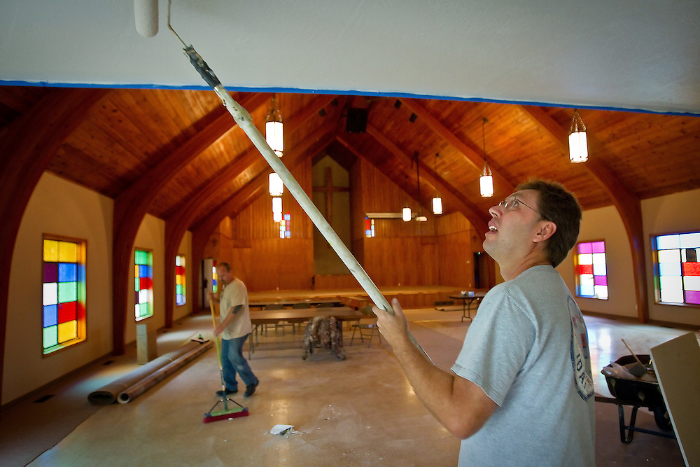 JEROME A. POLLOS/Press..Eric Wilder finishes painting a ceiling in the main sanctuary of the Heart of the City Church in Coeur d'Alene as Marty Coleman sweeps the floor Tuesday.