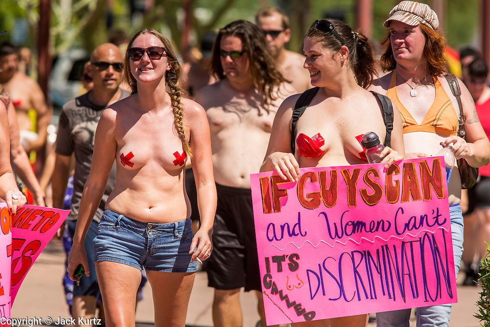 26 MARCH 2012 - PHOENIX, AZ:  JENNA DUFFY, left, and KELLY CAYE lead a march of topless women and men in Phoenix. About 40 people marched through central Phoenix Sunday to call for a constitutional amendment to give women the same right to go shirtless in public that men have. The Phoenix demonstration was a part of a national Topless Day of Protest. Phoenix prohibits women from going topless in public so protesters, women and men, covered their nipples and areolas with tape. The men did it to show solidarity with the women marchers.   PHOTO BY JACK KURTZ
