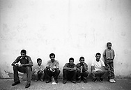 Seven men sitting and waiting by a wall, for the Theater Stap show to begin. Tafoghalt, Morocco, 2006