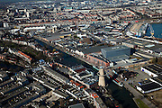 Nederland, Zuid-Holland, Schiedam, 20-03-2009; Mathenesse met de Buitenhaven en de jeneverstokerij- distilleerderij? van Nolet, producent van onder andere Ketel 1 jenever. De Noletmolen uit 2005-2006 is gebouwd in opdracht van Nolet Distillery. De molen heeft het uiterlijk van een historische stellingmolen en dient als blikvanger en ontvangstruimte voor het bedrijf. De molen, eigenlijk een windturbine, werkt volautomatisch en wekt elektriciteit op ten behoeve van de distilleerderij. Rechts Merwehaven en Oud Mathenesse (Rotterdam). Air view of Schiedam, in the center right the grey building of Nolet Dilstillery , producer of gin, Ketel 1 genever. The old Nolet mill ihas been changed into a modern wind energy mill and a reception room for Nolet..Swart collectie, luchtfoto (toeslag); Swart Collection, aerial photo (additional fee required).foto Siebe Swart / photo Siebe Swart