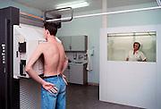 Nederland, Nijmegen, 15-10-1989Een patient laat een rontgenfoto maken van zijn borst. De verpleegkundige, staat achter een beschermende wand om niet teveel aan radioactiviteit blootgesteld te worden. Foto: Flip Franssen