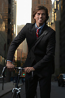 Smiling man standing by bicycle in street portrait