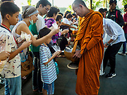 "17 MARCH 2018 - BANGKOK, THAILAND:  Buddhist monks collect alms from the crowd during a ""sticky rice merit making"" in Lumpini Park in Bangkok. Sticky rice merit making is a merit making in the Isan / Lao style, when people present small amounts of cooked sticky rice (also known as glutinous rice) to Buddhist monks. Isan is the northeast region of Thailand.    PHOTO BY JACK KURTZ"
