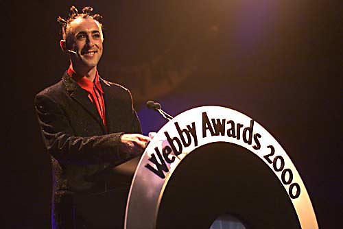 webby awards host alan cumming at the podium.