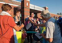 Host family Danny, Wendy and Tom Getchell-Lacey welcome Emily Axelsson and Jimena Silva outside the Laconia Middle School as Up With People arrives Monday evening.  (Karen Bobotas/for the Laconia Daily Sun)