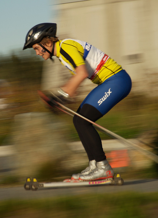 A roller-skiiing competitor sprints toward the finish line.