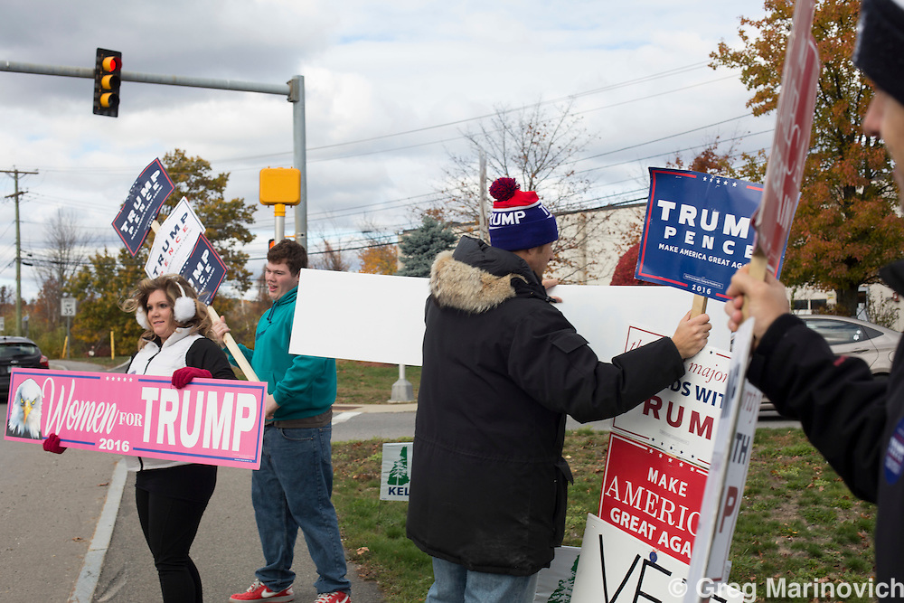 A family hold pro Donald Trump posters at an interstion in Derry, NH. Pre-election activites in New Hampshire state, where the first primaries were held that eventually led to Hillary Clinton and Donald Trump facing off in a highy charged presidential campaign two days before the final ballots must be cast. Photo Greg Marinovich