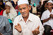 07 JULY 2013 - NARATHIWAT, NARATHIWAT, THAILAND:  A Thai Muslim man prays during a civil affairs project sponsored by Royal Thai Marines in Narathiwat Sunday. Royal Thai Marines in Narathiwat province held a special ceremony Sunday in advance of Ramadan. They presented widows, orphans and indigent people with extra rice and food as a part of the Thai government's outreach to resolve the Muslim insurgency that has wracked southern Thailand since 2004. The Holy Month of Ramadan starts on about July 9 this year. Muslims are expected to fast from dawn to dusk, engage in extra prayers, recitation of the Quran and perform extra acts of charity during Ramadan. It is the holiest month of the year for Muslims.  PHOTO BY JACK KURTZ