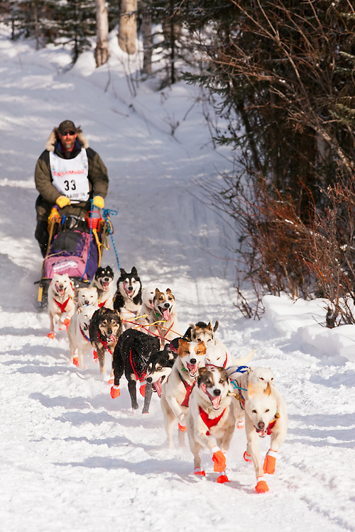 Musher Chris Adkins competing in the 38th Iditarod Trail Sled Dog Race entering Long Lake after leaving the Willow Lake area at the restart in Southcentral Alaska.  Afternoon.