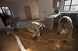 © Licensed to London News Pictures. 29/12/2015. York, UK.  Royal Electrical and Mechanical Engineer soldiers remove flood damaged flooring from a house in the centre of York on December 29, 2015. Further rainfall is expected over coming days as Storm Frank approaches the east coast of the country. Photo credit: Ben Cawthra/LNP