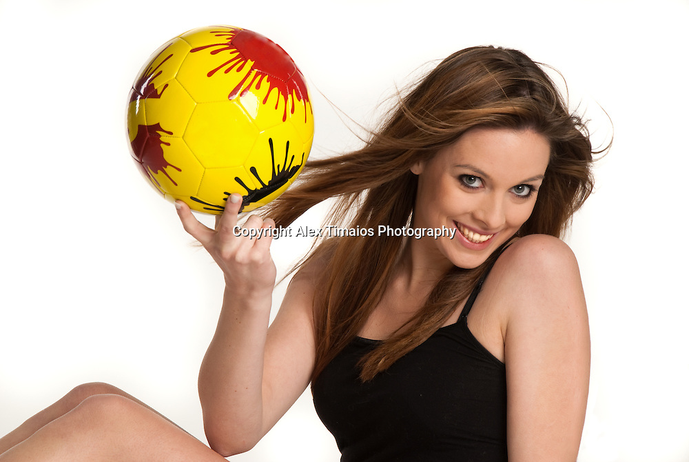 A pretty young girl holding a yellow ball in her hand
