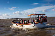 A Bean's small ferry takes tourists out in Blakeney Point a Natural Nature Reserve in North Norfolk, England, UK.  The boat trip is to view seals and birds in their natural environment.  Beautiful blue sky with white clouds.