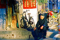 China, Taiyuan, 2008. An older man enjoys the afternoon sun in a traditional neighborhood alley. China's seniors are active until their very late years.