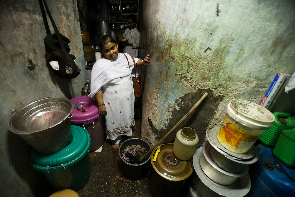 """Abida Sayyed 40 years old, looks on in her kitchen in the Razzaq chawl at the Behrampada area, in Mumbai, India, on Tuesday February 11, 2009. 40 years old. She is a short lady with an iron will, her husband left her with Talaq on the premise that she was short in stature. She had had two children with him. She was introduced to the Mandal when she got her caalways faltering, but after coming into the Mandal her confidence has soared. Her husband has only given her """"Jubani Talaq"""" (divorce by word). She says proudly """" I even slapped him once in front of the inspector. Now they all support me."""" Being a single women in the settlement area is tough. Her night duties and meeting with mandal ladies are generally misinterpretted. Her motto in her life is to educate her 19 year old daughter. Even her son had quit studying a while ago to support the home. She lives with her ailing mother. Her husband and his family have never contacted her or supported her since. Talking to males around is still a taboo for a single woman in her locality.se here. She had a 5 month old baby girl in her arms when she underwent Talaq proceedings. She never looked back since then. Taking life into hr own hands, Abida trained herself as a domestic help first, and then slowly got trained in nursing and now does private nurse services through the Holy Family Navjit community health center. She said she was very under confident of life before, her health was affected, today she can hold out on her own and challenge society. ."""