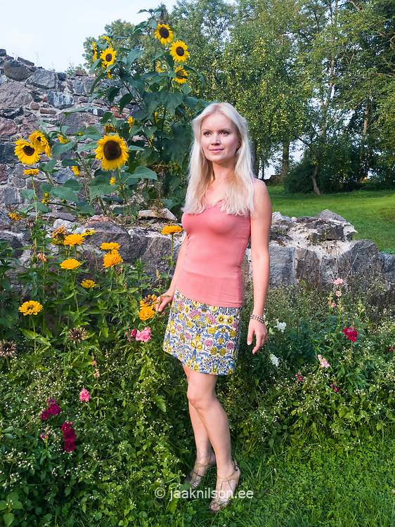 Blond hair woman standing in sunflowers