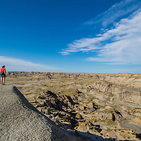 hiker on ridge with wispy clouds near dry arm fort peck lake badlands montana