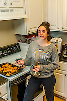 Young woman smoking marijuana in a bong in her kitchen, Aurora, Colorado USA. Colorado was the first state to legalize the sale of marijuana for recreational use in 2014.