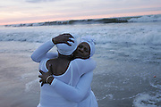 Two women embrace during an early morning seaside ceremony  in remembrance of the millions of  Africans who  perished  as they were being brought in brutal conditions to be slaves in the Americas.<br />