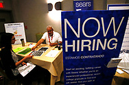 A job applicant (L) talks with a recruiter for Sears at a job fair in Golden, Colorado June 7, 2016. REUTERS/Rick Wilking