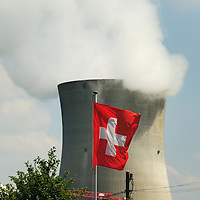 Swiss flag and the cooling tower of Leibstadt nuclear power station, with the top of the dome of the reactor is just visible at left. One of four sites in Switzerland, this plant stands close to the German border.<br />