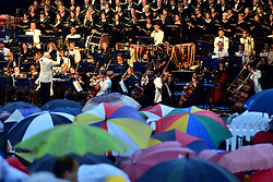 © Licensed to London News Pictures. 24/08/2013. London, UK Roderick Dunk conduct whilst the crowd watches from a sea of umbrellas. The Royal Choral Society together with the Royal Philharmonic Concert Orchestra, performs an evening of the choral classics in Heavy rain at Live by the Lake. The English Heritage concert season returns to Kenwood House in Hampstead, London, with Live by the Lake. The season includes Suede, a Choral Greats concert, Keane, an outdoor live screening of Singin' in the Rain featuring the Royal Philharmonic Concert Orchestra, Opera Alfresco and an evening of Gershwin. . Photo credit : Stephen Simpson/LNP