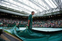 LONDON, ENGLAND - Monday, June 20, 2011: Groundstaff remove the rain covers after the roof closes on Centre Court, during the Ladies' Singles 1st Round match on day one of the Wimbledon Lawn Tennis Championships at the All England Lawn Tennis and Croquet Club. (Pic by David Rawcliffe/Propaganda)