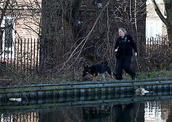 © licensed to London News Pictures. London, UK 08/03/2012. A Police officer and a dog search bushes next to Regents Canal in east London where a torso, thought to be that of TV actress Gemma McCluskie's  was found yesterday. Photo credit: Tolga Akmen/LNP