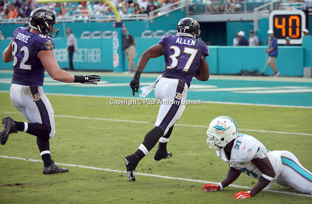 Baltimore Ravens tight end Nick Boyle (82) trails from behind as Baltimore Ravens running back Javorius Allen (37) avoids a tackle attempt by Miami Dolphins free safety Michael Thomas (31) on a 41 yard touchdown catch and run pass play that cuts the Dolphins third quarter lead to 15-10 during the 2015 week 13 regular season NFL football game against the Miami Dolphins on Sunday, Dec. 6, 2015 in Miami Gardens, Fla. The Dolphins won the game 15-13. (©Paul Anthony Spinelli)