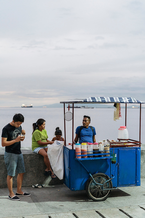 Alvin Gaji, with his wife Clarabel Hilario, and daughter Dynhice Riquez, 4, sell street food with sour dipping sauces along the wall in Manila Bay, Manila, Philippines.
