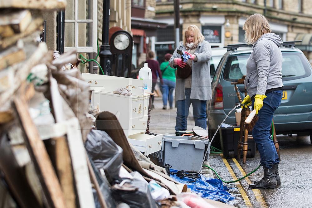© Licensed to London News Pictures. 28/12/2015. Hebden Bridge UK. A huge clean up operation has begun in Hebden Bridge after the River Calder broke it's banks & flooded homes & business' in the village centre. Photo credit: Andrew McCaren/LNP