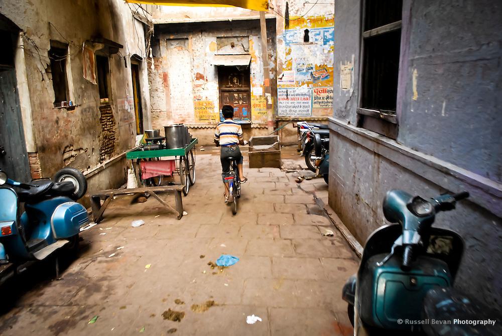 A young boy rides his bike through the narrow back alleys in Varanasi, Uttar Pradesh, India