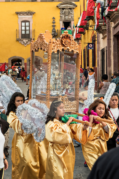 Costumed angels escort a statue of Saint Michael in a religious procession through the city at the start of the week long fiesta of the patron saint Saint Michael  September 21, 2017 in San Miguel de Allende, Mexico.