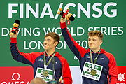 Tom Daley of Great Britain and Matty Lee of Great Britain smile on the podium and wave to the crowd after winning the Men's Syncronised 10m dive  during the FINA/CNSG Diving World Series 2019 at London Aquatics Centre, London, United Kingdom on 17 May 2019.