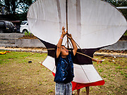 01 AUGUST 2017 - UBUD, BALI, INDONESIA:  A boy tries to hang on to a janggan (bird shaped) kite at the public school soccer field in Ubud. Kite flying is a popular past time on Bali. It originally had religious connotations, it was used to ask the gods for bountiful rains and harvests. The kites are large. Small ones, flown by individuals are about two meters long, larger ones flown by teams of up to 80 people are ten meters long. There are three shapes of traditional kites, bebean (fish-shaped), janggan (bird-shaped) and pecukan (leaf-shaped). The pecukan is the most unstable and difficult to fly.   PHOTO BY JACK KURTZ