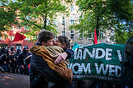 "01/05/2015 – Berlin, Germany: A couple kisses on the street while member of the radical left pass by during the ""Revolutionary 1st of May Demonstrations"" in Kreuzberg to celebrate the Workers Day. The International Workers Day is a celebration of laborers and the working classes that is promoted by the international labor movement, anarchists, socialists, and communists and occurs every year on May Day. (Eduardo Leal)"