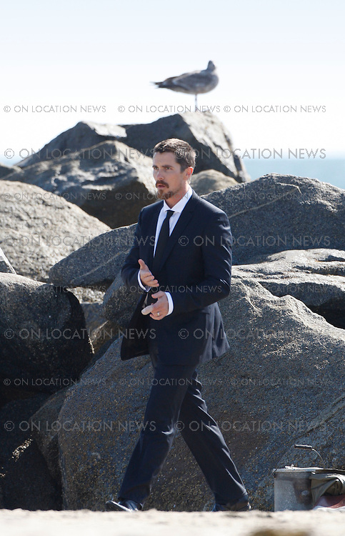 VENICE BEACH, CALIFORNIA - THURSDAY 12TH MARCH 2009. **EXCLUSIVE**: Batman star Christian Bale posing for a photo shoot at Venice Beach. Bale was photographed wearing a suit while holding a fishing rod & pretending to cast. In between shots he drank from a bottle of beer and chatted with his wife, Sandra Blazic, who appeared to be there for support. Bale appeared to be pretty stiff and tense in the first few minutes of shooting. After quickly downing an entire bottle of beer Bale then seemed much more relaxed and animated for the rest of the shoot while also enjoying more beer in between set ups.  Sales: Eric Ford 1/818-613-3955 info@OnLocationNews.com