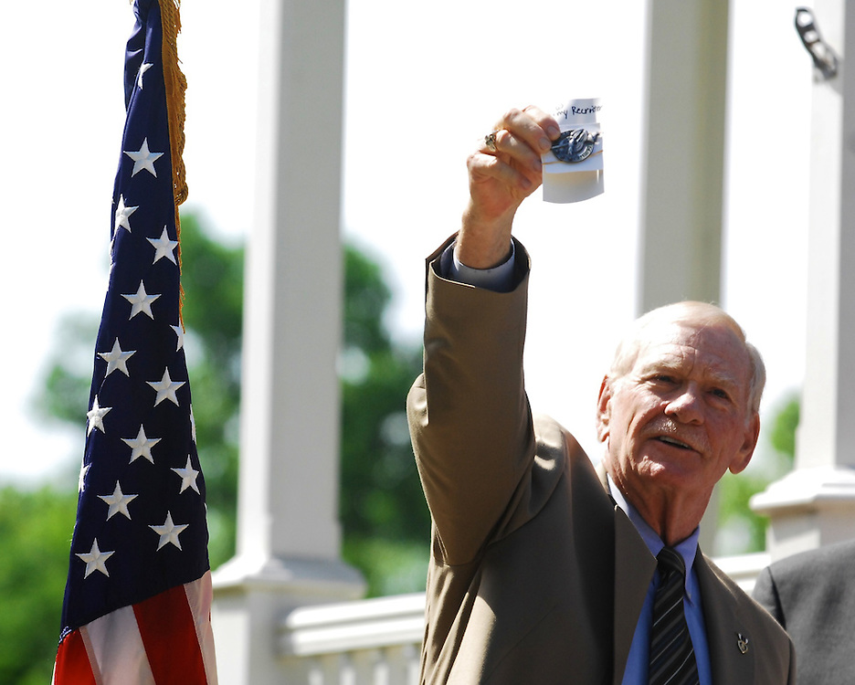 """Sgt. David Hack, holds up the Army Recruiter badge, telling the crowd, """"I am proud of this one.""""  After returning from Vietnam in 1969, Hack returned to Akron where he worked as a recruiter until he was honorably discharged in 1973."""