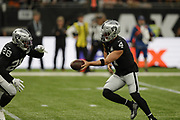 Derek Carr (QB) of the Oakland Raiders Josh Jacobs (RB) of the Oakland Raiders passing football during the International Series match between Chicago Bears and Oakland Raiders at Tottenham Hotspur Stadium, London, United Kingdom on 6 October 2019.