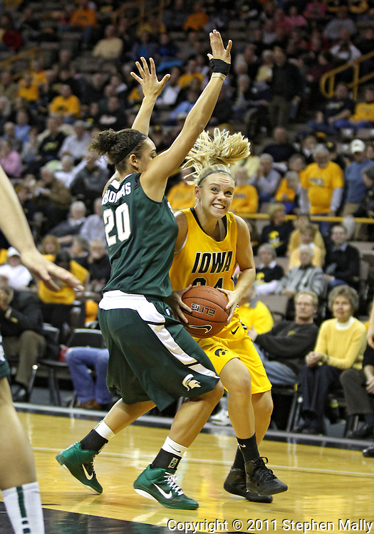 January 27 2010: Iowa guard Jaime Printy (24) eyes the basket as she tries to get around Michigan St. guard Brittney Thomas (20) during the first half of an NCAA women's college basketball game at Carver-Hawkeye Arena in Iowa City, Iowa on January 27, 2010. Iowa defeated Michigan State 66-64.