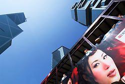 Striking billboard of womans face on side of Hong Kong Tram with skyscrapers to rear