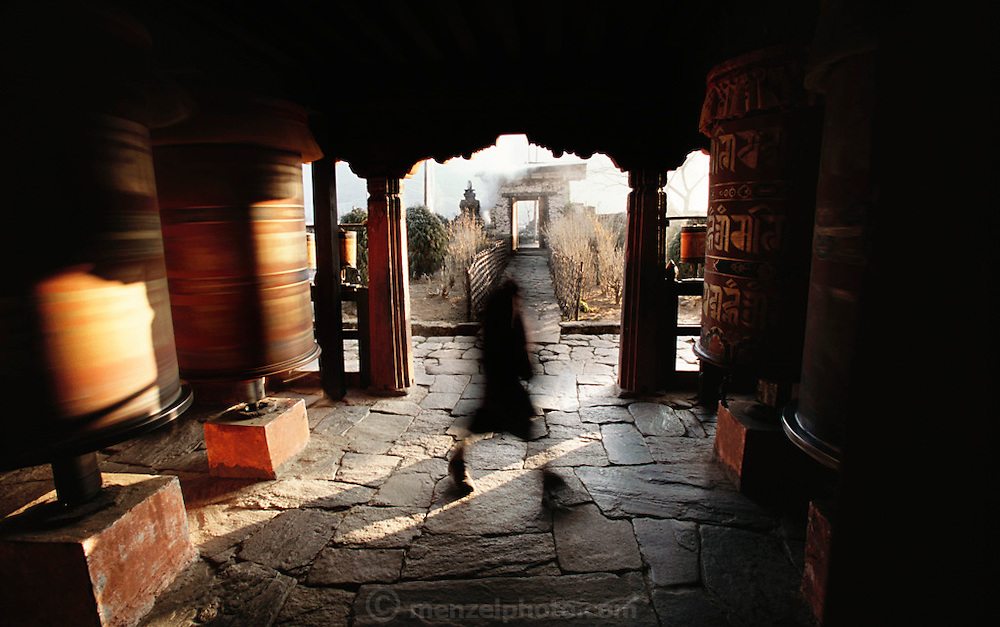 A visitor spins one prayer wheel then moves to another until all four in an entry at Jambey Khakhang are spinning. The spinning cylinders are filled with prayers, which are ?said? as the wheel turns. Bumthang Valley, Bhutan. From coverage of revisit to Material World Project family in Bhutan, 2001.