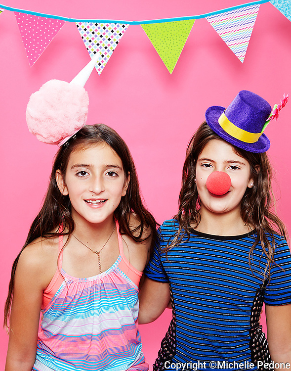2 tween girls wearing clown hat and cotton candy hat against pink seamless<br /> Photographed at Photoville Photo Booth September 20, 2015
