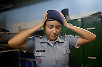Police Pacification Unit (UPP) officer Mariana Gomes prepares for her patrol shift in Complexo do Caju, a complex of a newly pacified favelas in the North Zone, Rio de Janeiro, Brazil, on Saturday, April 27, 2013. <br />