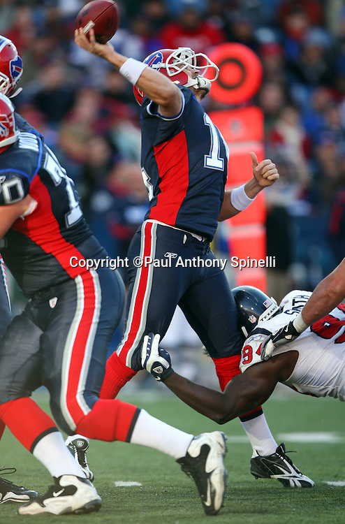 Buffalo Bills quarterback Ryan Fitzpatrick (14) gets hit with a helmet on his knee while throwing a deep pass during the NFL football game against the Houston Texans, November 1, 2009 in Orchard Park, New York. The Texans won the game 31-10. (©Paul Anthony Spinelli)