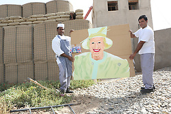 © Licensed to London News Pictures. 29/05/2012, Lashkar Gah, Afghanistan. Chefs working for the British military in Afghanistan hold up a portrait of the Queen as he prepares decorations for a street party in the military base.  Photo credit : Alison Baskerville