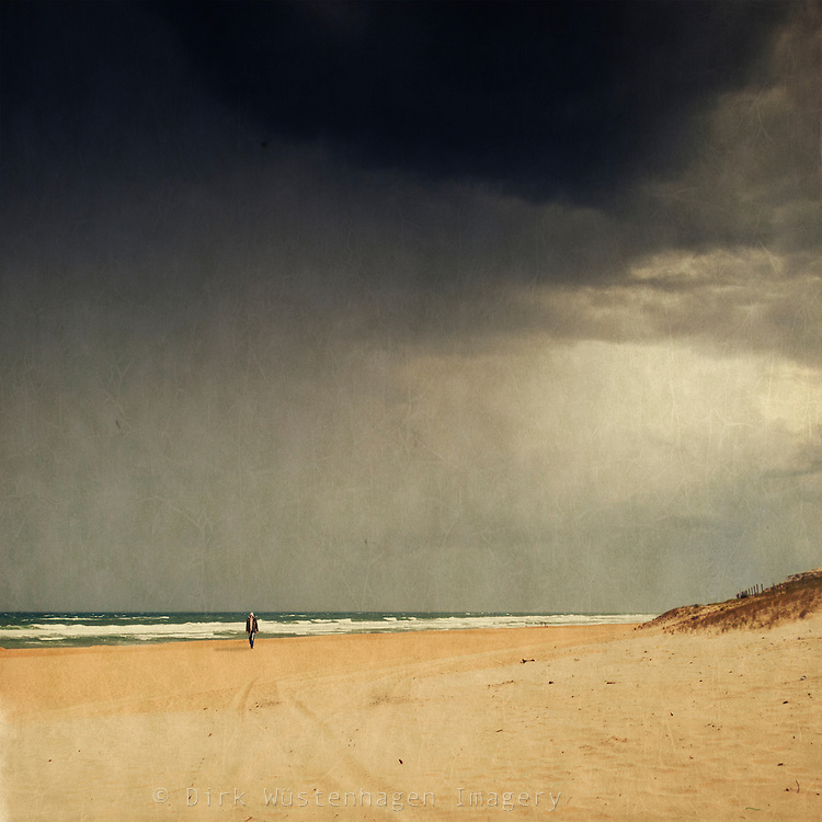 Man walking on a deserted beach - texturized photograph<br />