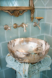 Sterling silver bath wash basin with light blue tile bathroom