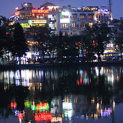 The lights of Hanoi's Old Quarter reflect on the still waters of Hoan Kiem Lake (Ho Hoan Kiem) at night. The lake's wall at this end is ringed with spotlights that change color. Behind are the lights from tourist bars and restaurants with a view out over the lake.