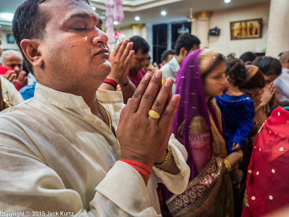 05 SEPTEMBER 2015 - BANGKOK, THAILAND:  A man prays during Janmashtami services in the Vishnu Temple in Bangkok. Janmashtami is the annual celebration of the birth of the Hindu deity Krishna, the eighth avatar of Vishnu. Hindus celebrate Janmashtami by fasting, worshipping Krishna and staying up until midnight, the time when Krishna is believed to have been born. At midnight they pray and exchange small gifts.    PHOTO BY JACK KURTZ